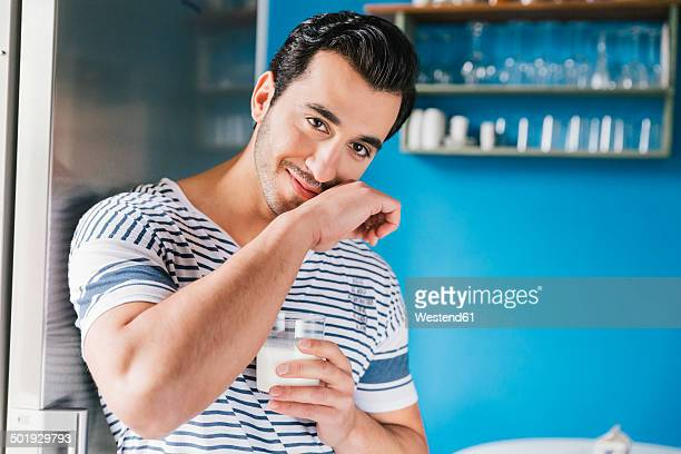 Portrait of smiling young man wiping off his milk moustache