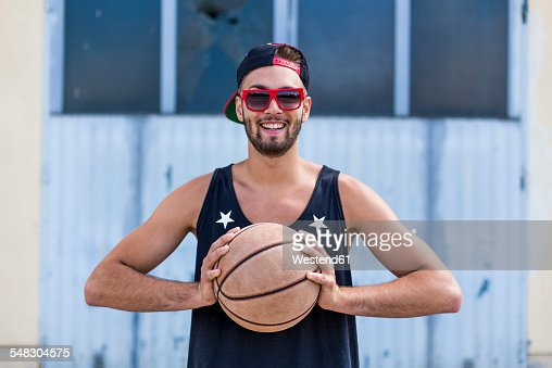 Portrait of smiling young man with basketball wearing basecap and sunglasses