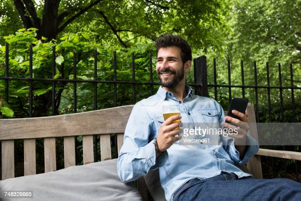Portrait of smiling young man with cell phone and glass of beer relaxing in garden