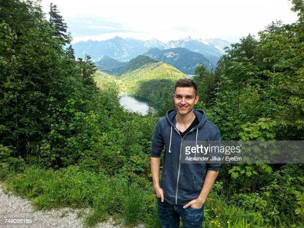 Portrait Of Smiling Young Man With Hands In Pockets Standing On Mountain In Forest