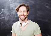 Portrait of smiling young man with headphones in front of chalkboard