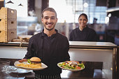 Portrait of smiling young waiter serving food while standing against waitress at counter in coffee shop