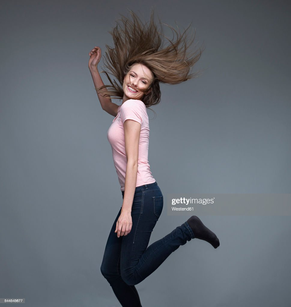 Portrait of smiling young woman dancing in front of grey background