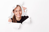 Portrait of smiling young woman emerging from paper