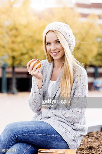 Portrait of smiling young woman holding an apple wearing wooly hat and cardigan