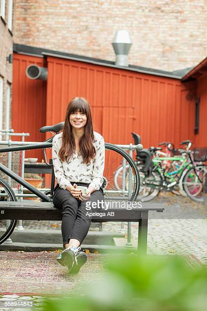 Portrait of smiling young woman holding coffee cup while sitting on bench at cafe backyard