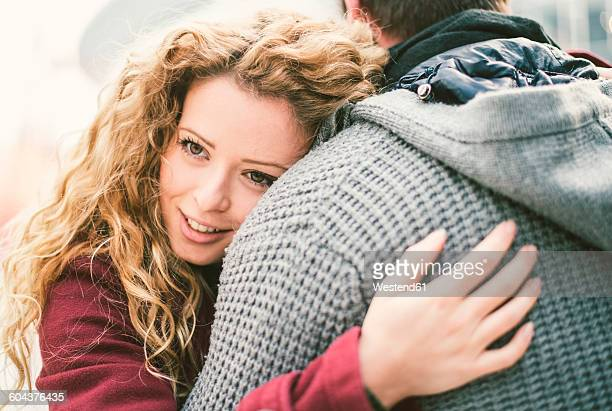 Portrait of smiling young woman hugging her boyfriend