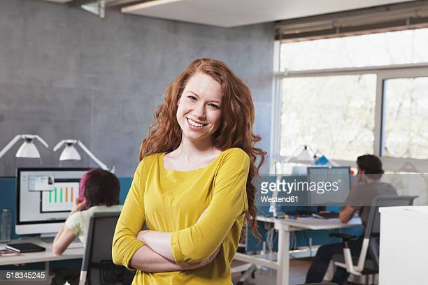 Portrait of smiling young woman in open space office