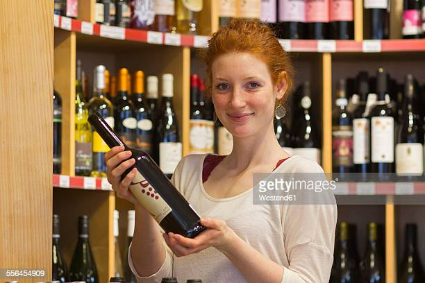 Portrait of smiling young woman in wholefood shop holding wine bottle