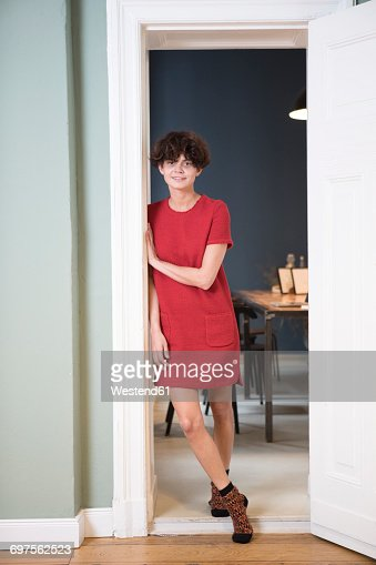 Portrait of smiling young woman leaning against door frame at home