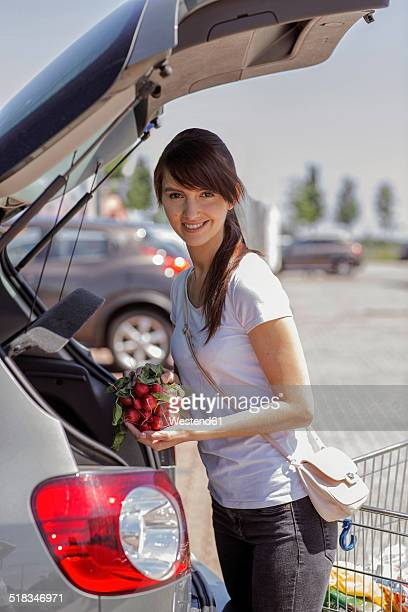Portrait of smiling young woman loading purchase in her car