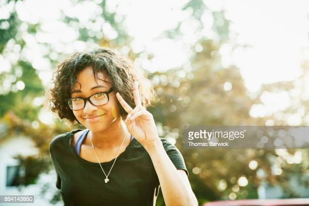 Portrait of smiling young woman making peace sign with fingers on summer evening