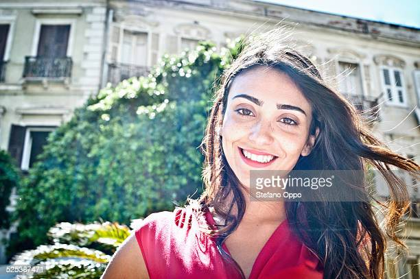 Portrait of smiling young woman on street, Cagliari, Sardinia, Italy