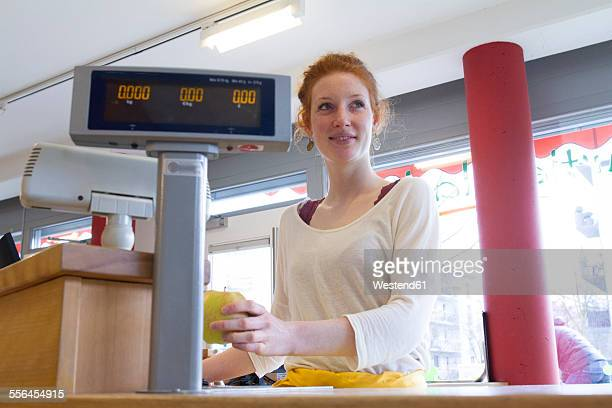 Portrait of smiling young woman sitting at counter of wholefood shop