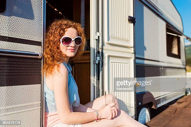 Portrait of smiling young woman sitting at entrance of caravan
