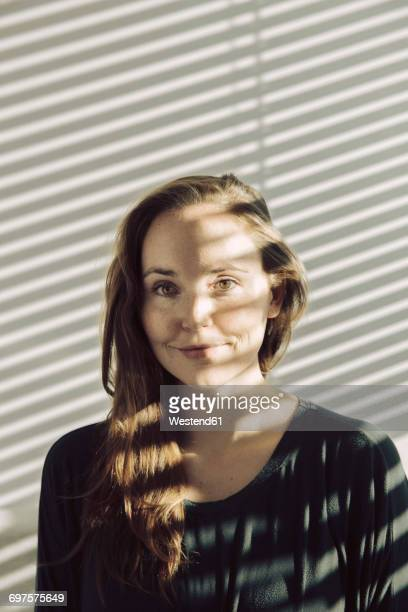 Portrait of smiling young woman sitting in a shadowed room