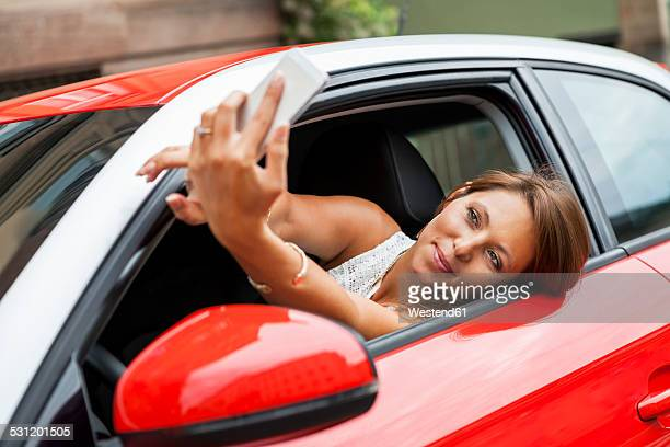 Portrait of smiling young woman sitting in her car taking a selfie with her smartphone