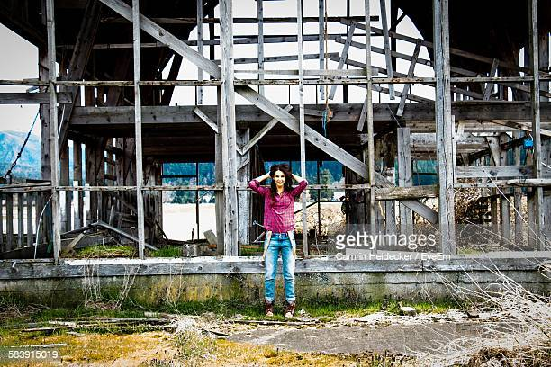 Portrait Of Smiling Young Woman Standing Against Abandoned House