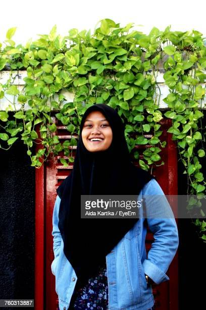 Portrait Of Smiling Young Woman Standing Against Wall At House Of Sampoerna