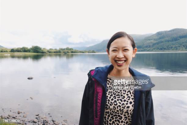 Portrait Of Smiling Young Woman Standing By Lake Against Sky