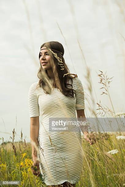 Portrait of smiling young woman standing on flower meadow