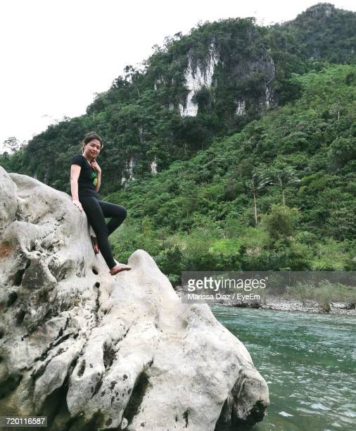 Portrait Of Smiling Young Woman Standing On Rock Formation By River