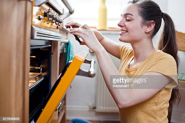 Portrait of smiling young woman taking a photograph of pastries in her oven