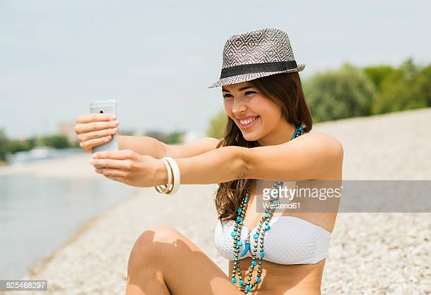 Portrait of smiling young woman taking a selfie with her smartphone on the beach