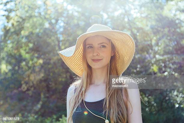 Portrait of smiling young woman wearing summer hat