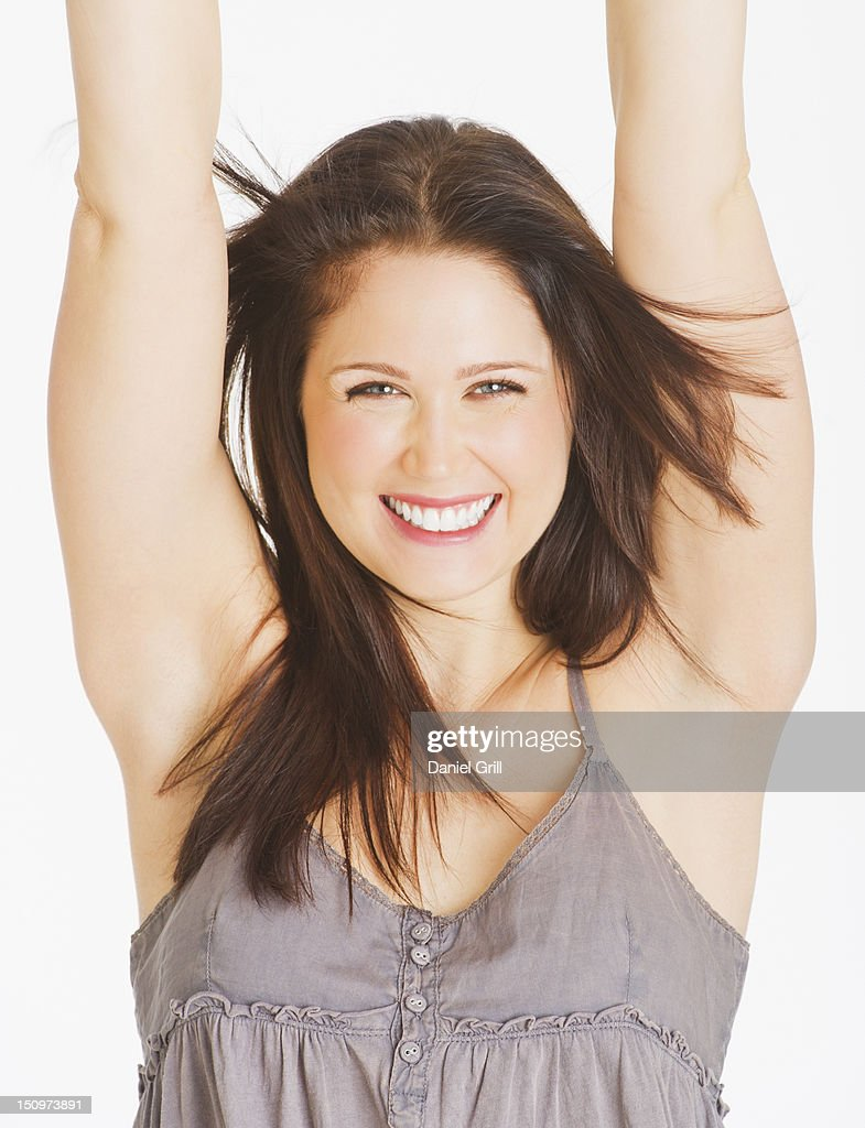 Portrait of smiling young woman with arms up, studio shot : Stock Photo