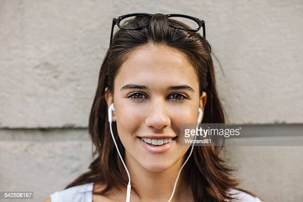 Portrait of smiling young woman with ear phones