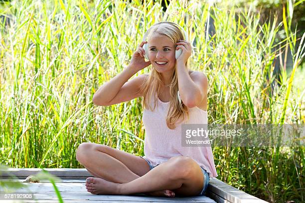 Portrait of smiling young woman with headphones sitting on wooden boardwalk