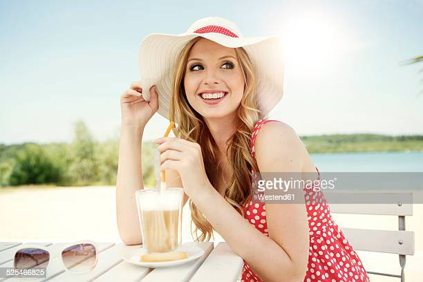 Portrait of smiling young woman with Latte macchiato