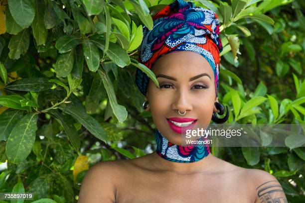 Portrait of smiling young woman with piercings wearing traditional Brazilian headgear