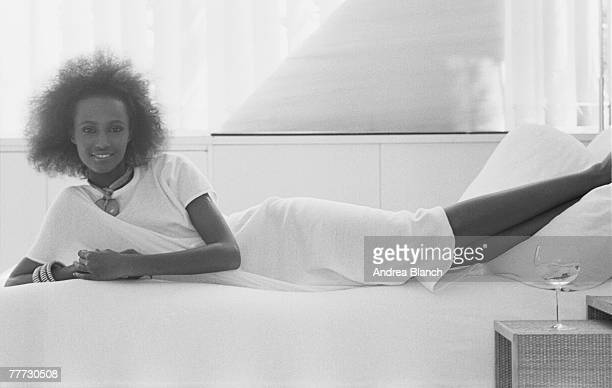 Portrait of Somaliborn American actress and model Iman as she lies on a bed her feet on the pillow from a photoshoot for the American edition of tfe...