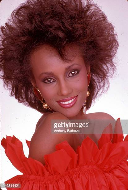 Portrait of Somaliborn American fashion model Iman dressed in red ruffled strapless top as she poses against a white background New York New York 1981
