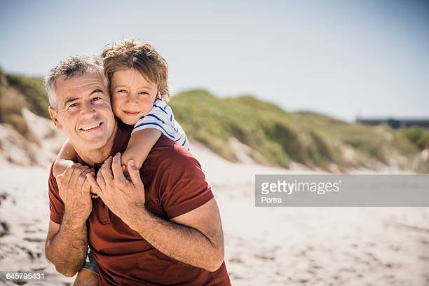 Portrait of son and father embracing at beach