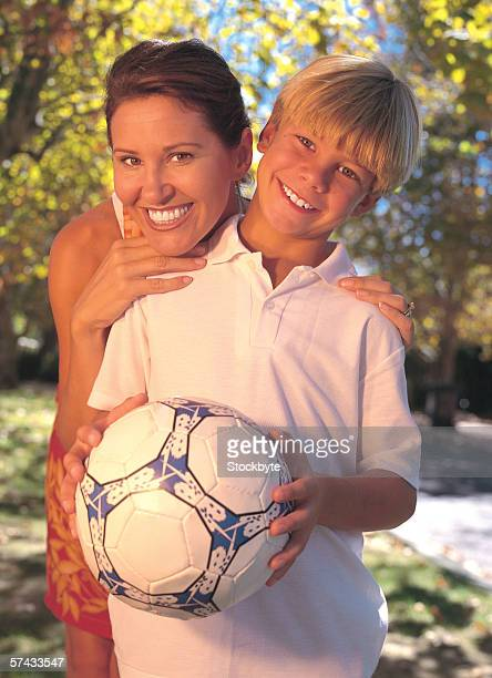 portrait of son holding a football and standing with his mother