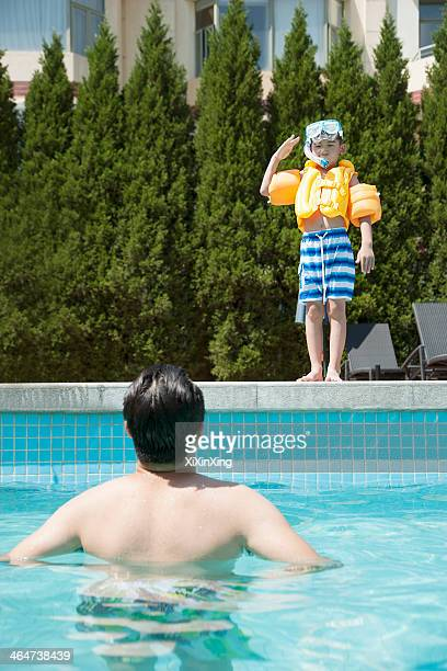 Portrait of son with snorkeling equipment standing by the pool as father waits in the water
