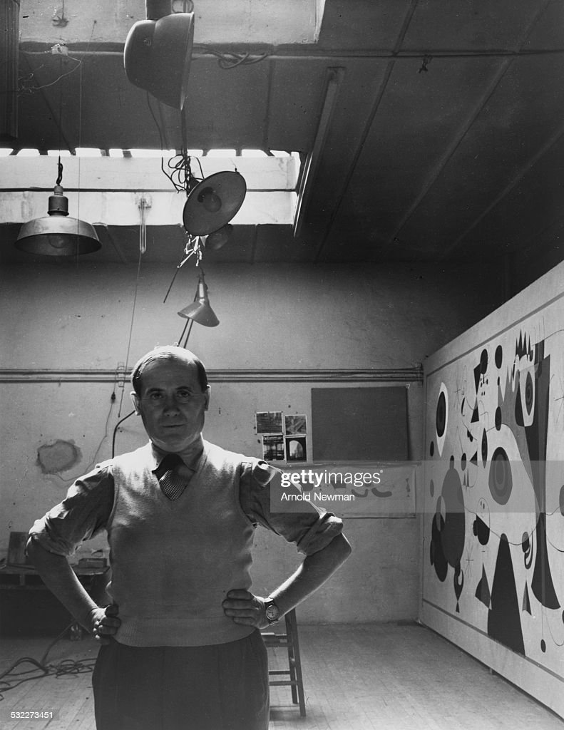 Portrait of Spanish artist <a gi-track='captionPersonalityLinkClicked' href=/galleries/search?phrase=Joan+Miro&family=editorial&specificpeople=190767 ng-click='$event.stopPropagation()'>Joan Miro</a> (1893 – 1983) as he poses, hands on his hips, in front of one of his paintings in Carl Holty's studio, New York, New York, September 1947.