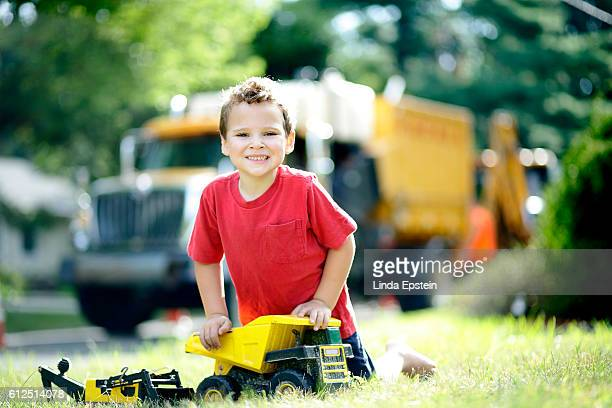 Portrait of special needs boy playing with his toy trucks