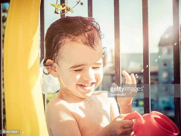 Portrait of splashing little girl on summers day