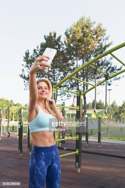 Portrait of sporty woman taking a selfie in the park