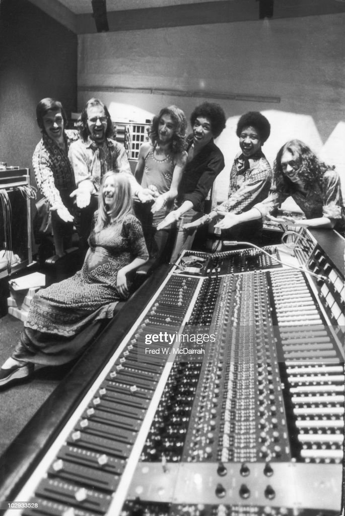 Portrait of, standing from left, American studio manager Jim Marron, South African-born American music producer and engineer Eddie Kramer, English musician Mitch Mitchell (1947 - 2008), American musician Jimi Hendrix (1942 - 1970), American musician Billy Cox, and Eglish musician Noel Redding (1945 - 2003), as they mile and gesture towards an unidentified pregnant woman who laughs as she sits behind the mixong board at Hendrix's then still under construction Electric Lady Studio, New York, New York, June 17, 1970. Mitchell, Cox, and Redding all played with Hendrix as part of the Jimi Hendrix Experience.