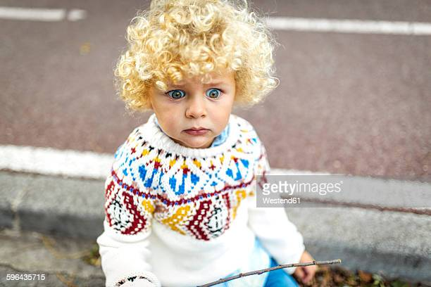 Portrait of starring blond little boy wearing patterned knit pullover