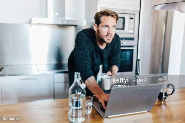 Portrait of starring man with coffee mug and laptop standing in kitchen