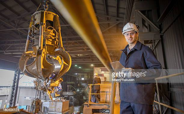 Portrait of steel worker overseeing mechanical grabber in steel foundry