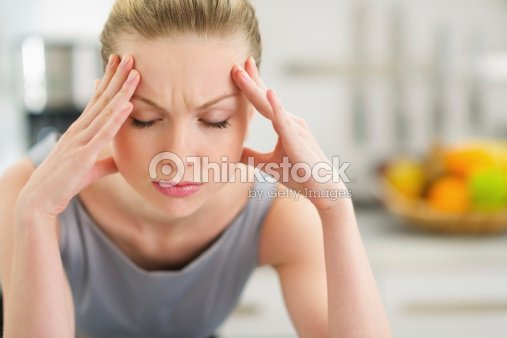 Portrait of stressed young housewife in modern kitchen : Stock Photo