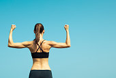 Portrait of strong female flexing muscles. Fitness concept.