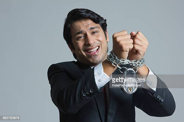 Portrait of struggling businessmans hand tied in chain over gray background